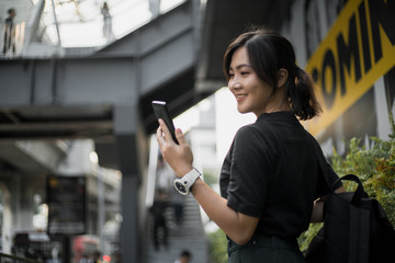 Happy asian woman looking at her phone in the city