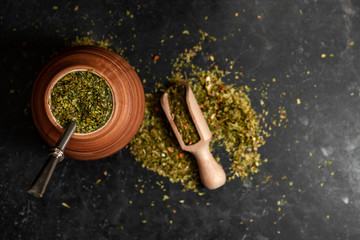Beautiful composition of yerba mate on a black background - Juicy and green leaves without sticks