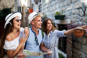 Smiling gorup of friends with map. Tourism, travel, leisure, holidays and friendship concept Wall mural