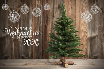 German Calligraphy Frohe Weihnachten Und Ein Glueckliches 2020 Means Merry Christmas And Happy New Year 2020. Christmas Tree Infront Of Brown Rustic Wooden Background With Decoration
