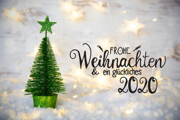 German Calligraphy Frohe Weihnachten Und Ein Glueckliches 2020 Means Merry Christmas And A Happy 2020. One Green Christmas Tree With Star Ornament. Sparkling Lights Background With Snow