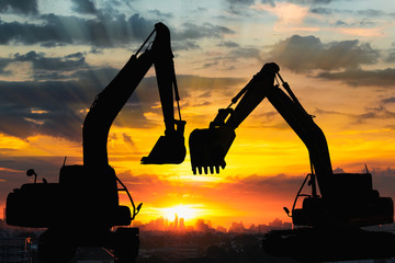Silhouettes two excavator with sunlight background of sunset in cityscape