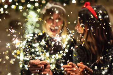 Portrait of 2 young women with glamor clothes and confetti and sparklers celebrating a party together with sparklers and lights