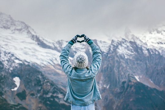 Young traveler girl in gloves standing over mountain peaks and making heart by hands