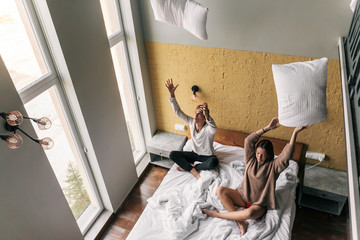 Young girl and guy relaxing on comfy bed in modern hotel room