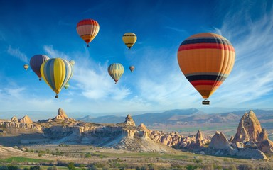 Poster Ballon Colorful hot air balloons fly in blue sky over amazing valleys with fairy chimneys in Cappadocia, Turkey