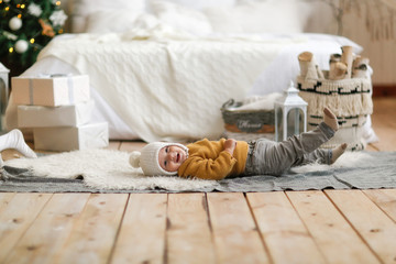 Funny baby in hat and sweater lies near the bed