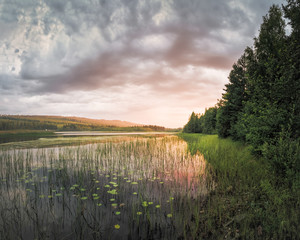 Panorama of vibrant color sunset over river and forest landscape Sweden