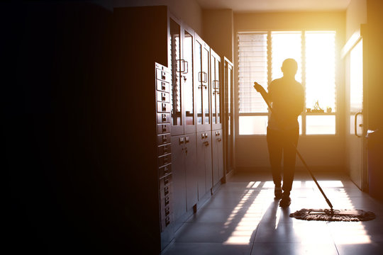 Janitor woman mopping floor in hallway office building or walkway after school or classroom with copy space. Silhouette housekeeper working job with sun light background.