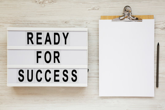 'Ready for success' words on a modern board, clipboard with blank sheet of paper on a white wooden background, top view. Overhead, from above, flat lay.