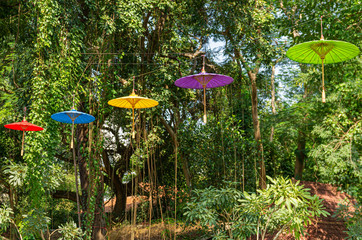 Picture of umbrellas hanging in a row with trees in the background for Loi Krathong festival