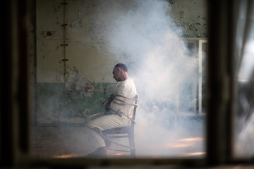 A crazy man in a straitjacket is tied to a chair in an abandoned old clinic