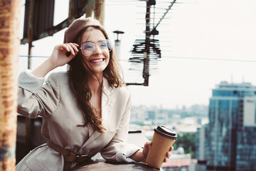 beautiful smiling girl in beige suit and beret posing on roof with coffee to go Wall mural