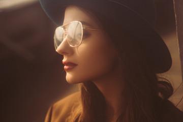 beautiful retro girl posing in eyeglasses and hat on urban roof