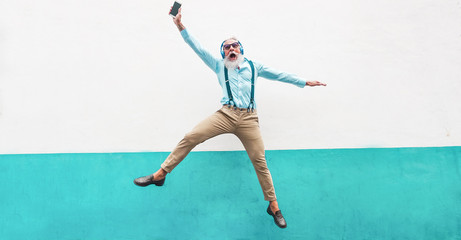Senior crazy man jumping and listening music outdoor - Happy mature male celebrating and dancing...