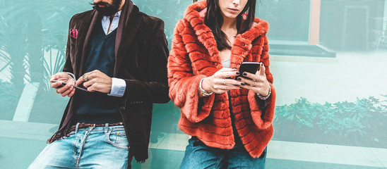 Fashion influencers people using smartphone social media app - Young trendy couple watching story...