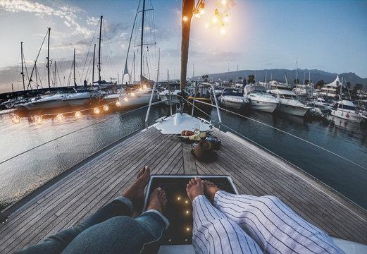 Legs view of senior couple having holidays on sail vintage boat - 60's trendy people enjoying a romantic vacation  - Travel, luxury, joyful elderly lifestyle and love concept - Focus on feet