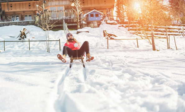 Young woman speeding with vintage sledding on snow high mountain - Happy girl having fun in white week vacation with chalet in background - Travel, winter sport, holiday concept - Focus on her face