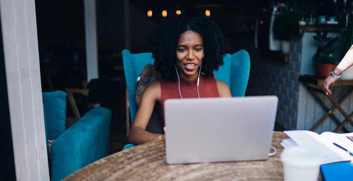 Positive black hipster girl in earphones listening positive audio book via application on laptop device during chatting with followers from social networks, happy woman choosing music playlist