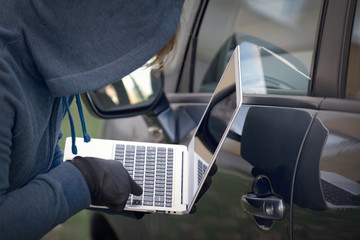 Hooded thief tries to break the car's security systems with laptop.