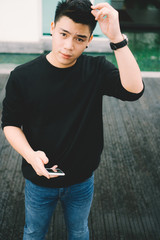 Young man fixing his hair and checking phone