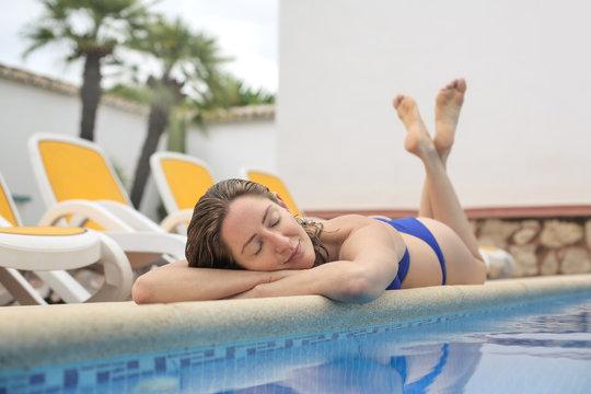 Beautiful girl resting on the swimming pool's ledge
