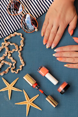 French Golden orange manicure on long oval nails with decorative cosmetics and sunglasses.Marine nail design.