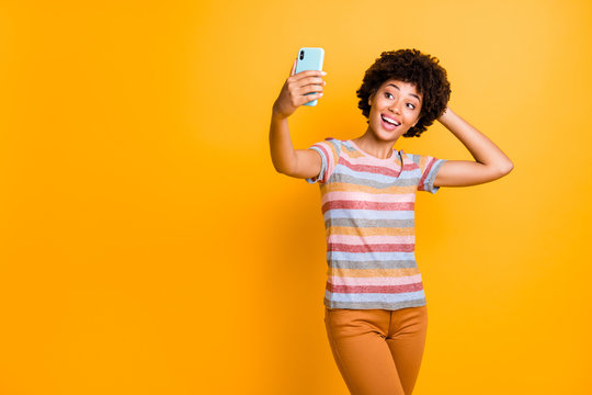 Photo of wavy cute nice charming pretty sweet girlfriend wearing pants trousers orange taking selfie excited about having bought new phone isolated over vibrant color background