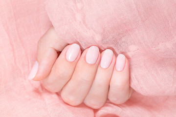 Closeup top view of beautiful one white female hand with natural manicured five fingers. Modern pastel gel polished nails isolated on pink delicate texture of fabric. Horizontal photography.