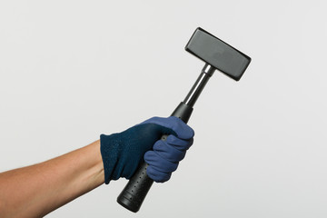 hand in working glove is holding a hammer