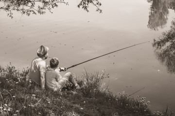 Back view of happy family on summer vacations concept. Father and son fishing together at river...
