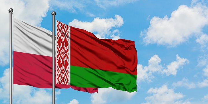 Poland and Belarus flag waving in the wind against white cloudy blue sky together. Diplomacy concept, international relations.
