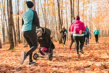 Stroller woman group out running together in an autumn park they run a race or train in a healthy...
