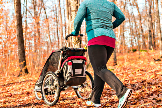 Stroller woman running in an autumn park they run a race or train in a healthy outdoors lifestyle concept