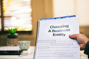 A document on different types of business formations being read by a small business owner while sitting in office desk.