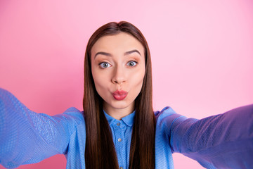 Self portrait of charming cute nice cheerful girlfriend kissing someone she talks with by video call wearing blue shirt isolated over pink pastel background