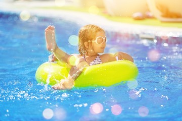 Children playing in pool. Two little girls having fun in the pool. Summer holidays and vacation...