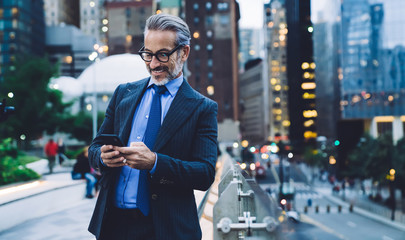 Mature satisfied male using mobile on urban background
