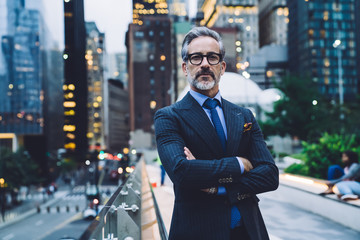 Confident mature businessman with arms crossed against evening New York street Fototapete