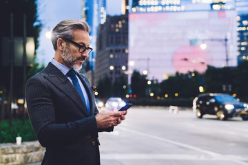 Adult businessman typing on smartphone against New York road