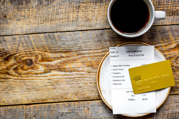 restaurant bill paying by credit card for coffee on wooden table background top view mock-up