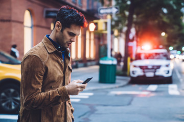 Thoughtful ethnic young man in jacket texting and walking along street Wall mural
