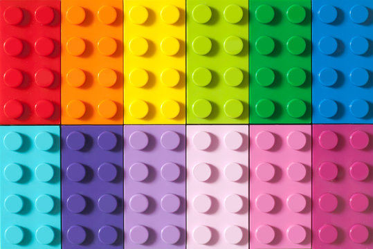 Many toy blocks in different colors making up one large square shape in top view. Toys and games. Leisure and recreation.