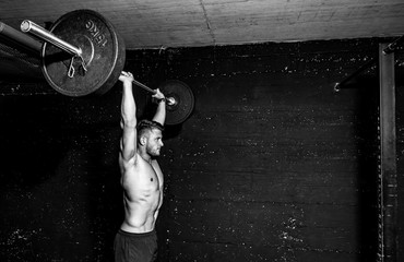 Young strong fit muscular sweaty man with big muscles doing barbell weight lifting cross training workout in the gym dark image real people black and white