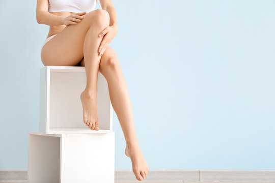 Woman with beautiful legs after depilation on color background