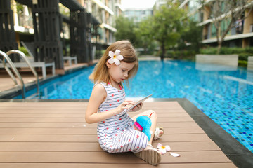 kid girl make photo on tablet sitting close to swimming pool wea
