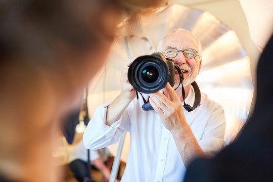 Photographer with digital camera takes portrait photos