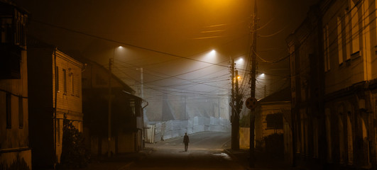 Lonely woman walking in foggy old city with street lights in a coat Fotomurales