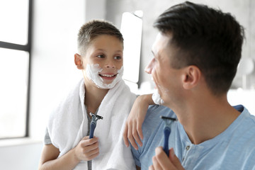 Happy father and son with shaving foam on their faces in bathroom