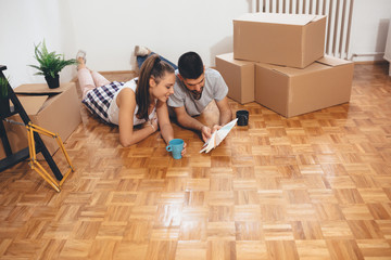 happy young family moving in their new home. choosing the color for interior walls